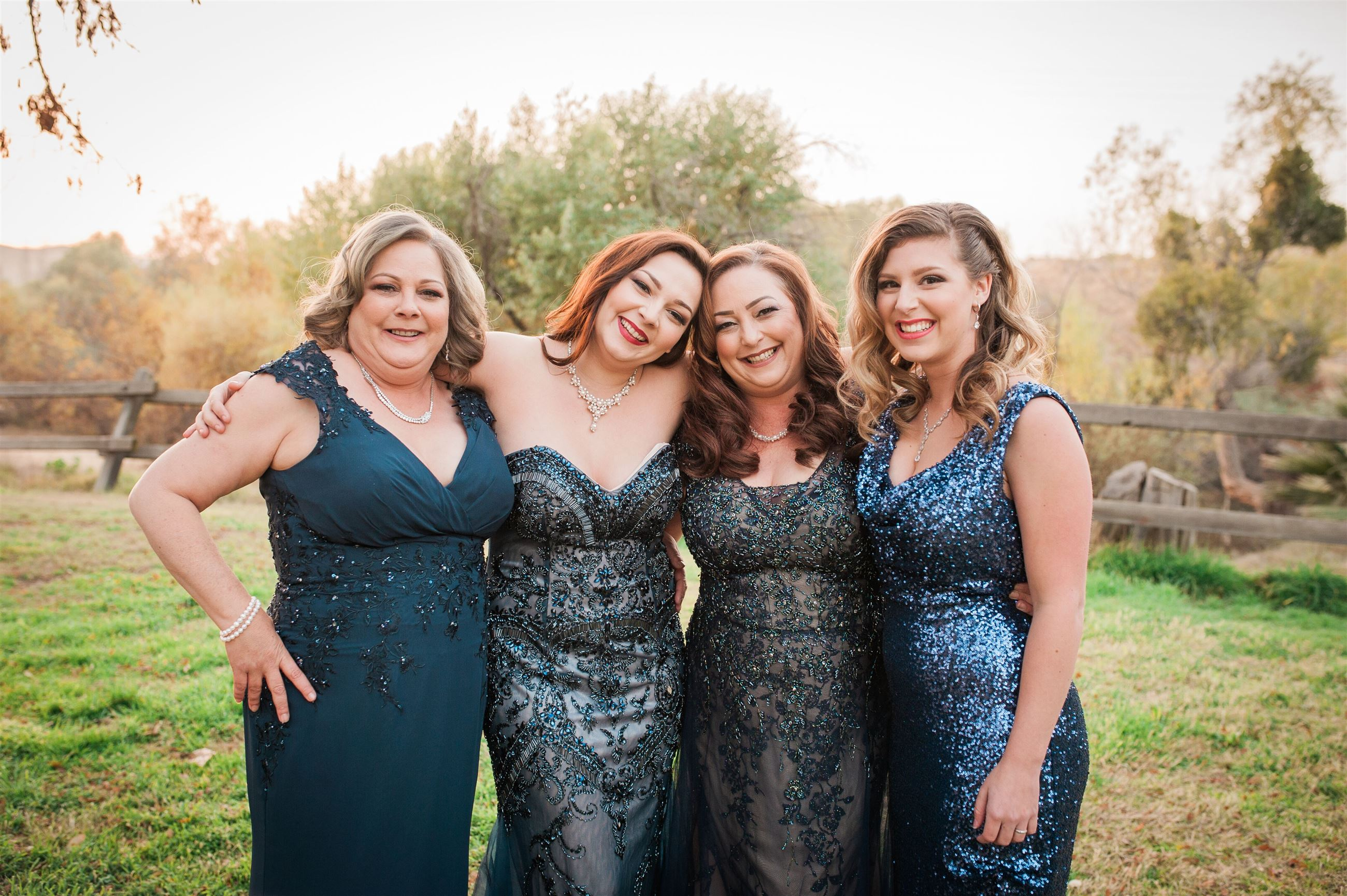 Four happy women wearing blue evening dresses in different styles