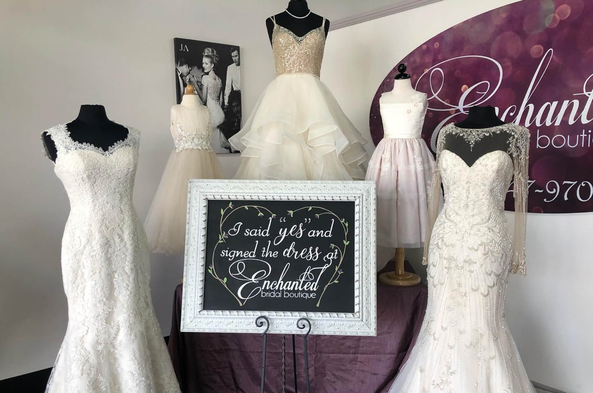 Three wedding dresses on display and two flower girl dresses on display at Enchanted Bridal shop