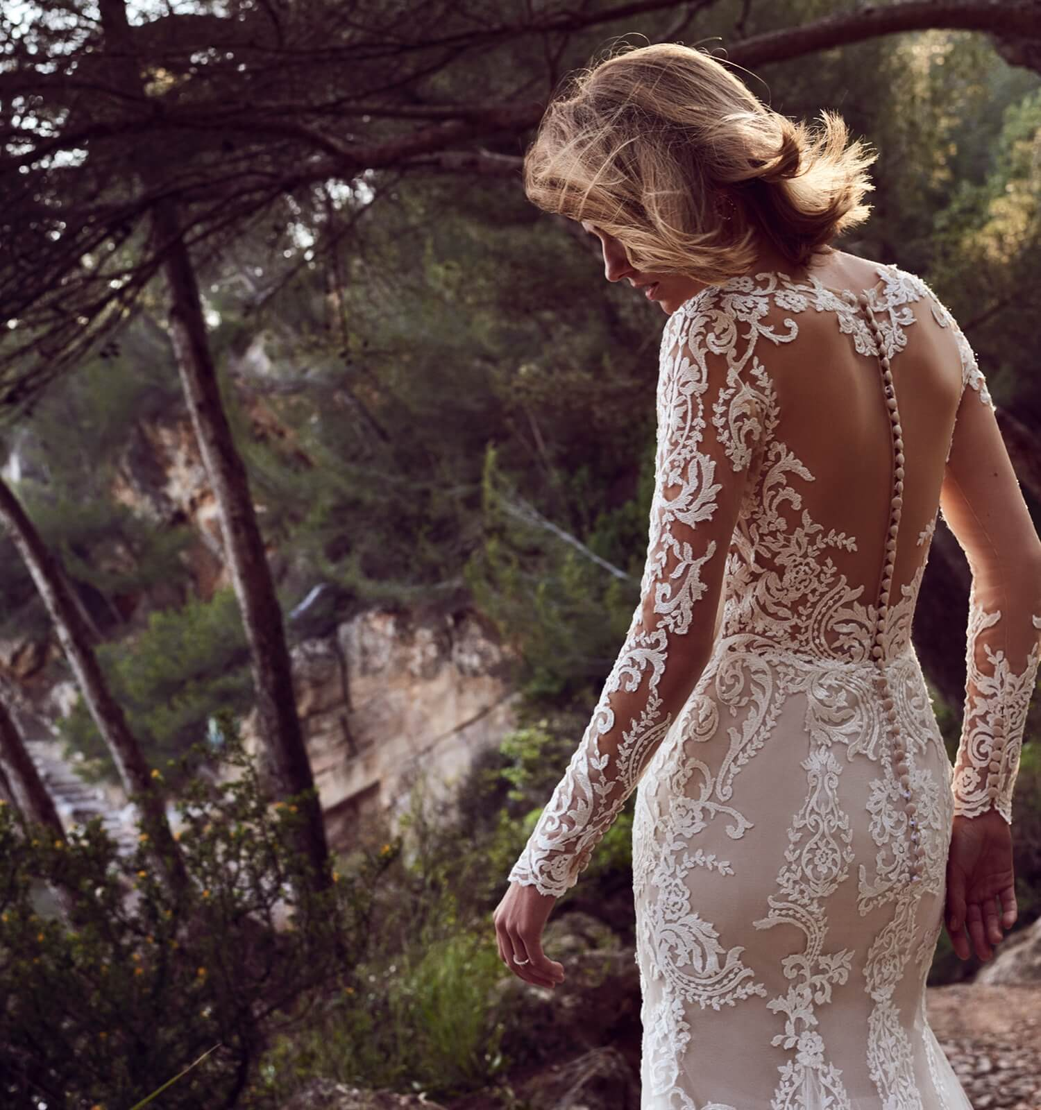 Model wearing lace long sleeve wedding dress shown on mobile device